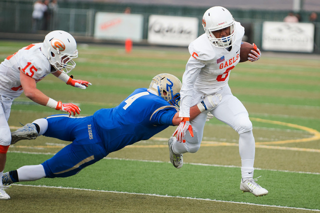 Bishop Gorman's Austin Arnold (6) breaks a tackle from Reed's Dylan Morell (4) allowing him to score during the first half of the NIAA Nevada State High School Division I Championships game at Dam ...