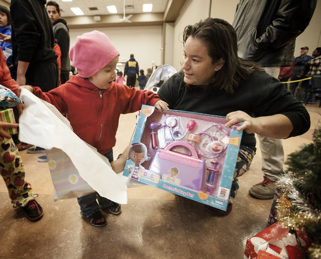 Diana Velazquez,3, left, unwraps the Doctor's Bag Set gift at the Rescue Mission, 480 West Bonanza Road, while her mother Sandra assists on Saturday, Dec. 20, 2014.  Velazquez has ten children ran ...