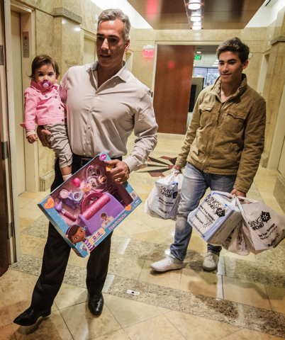Tony Carro holds his daughter Sunnye, 20 months, while carrying the Doctor's Bag Set gift to the Wells Fargo Corporate Office drop off location inside the Las Vegas Tower, 3800 Howard Hughes Parkw ...