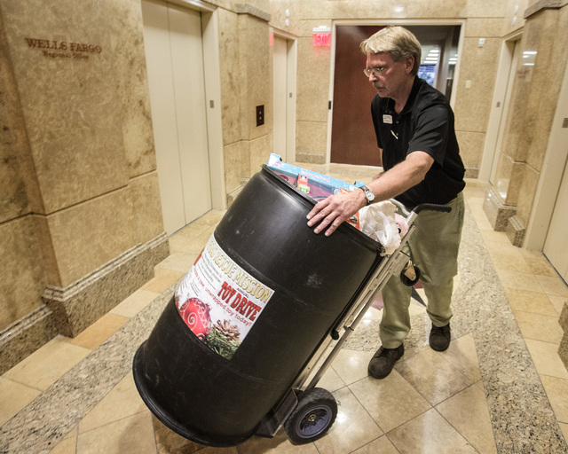 Andrew Musche hauls a barrel containing the Doctor's Bag Set gift  from the Wells Fargo Corporate Office inside the Las Vegas Tower, 3800 Howard Hughes Parkway on Wednesday, Dec. 17, 2014. They lo ...