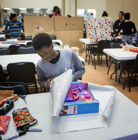 Denzil Dixon, 15, a volunteer with Batteries Included Leadership Program, wraps the Doctor's Bag Set gift at the Rescue Mission, 480 West Bonanza Road, on Wednesday, Dec. 17, 2014. This is the fir ...