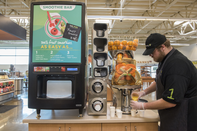 Employee Aaron White pours fresh orange juice to give as samples for customers inside the Fresh and Easy supermarket on 4760 W. Cactus Ave. in Las Vegas Friday Dec. 5, 2014. (Martin S. Fuentes/Las ...