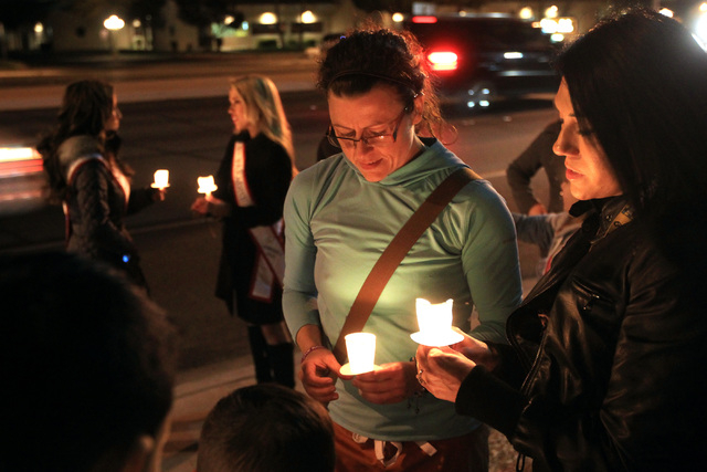 Kimi Monoco, center, and Rachel Sanchez take part in a candlelight vigil for Hailee Lamberth Thursday, Dec. 11, 2014. Hailee committed suicide a year earlier as a result of being bullied.  (Sam Mo ...