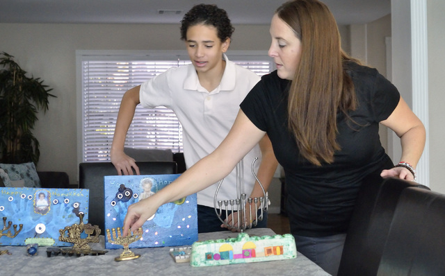 Miles Sims, left, helps his mother Davida unpack some Hanukkah-related holiday decorations at their home near West Lake Mead Boulevard and Harbor Island Drive in Las Vegas on Saturday, Dec. 6, 201 ...