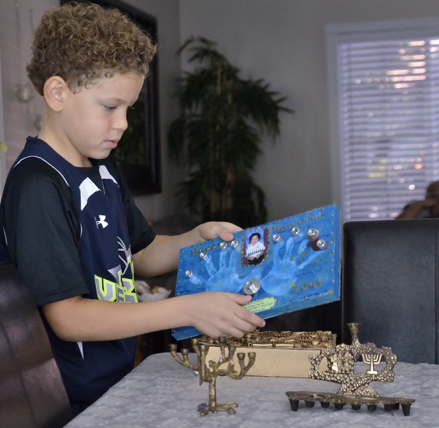 Cole Sims helps unpack some Hanukkah-related holiday decorations at his home near West Lake Mead Boulevard and Harbor Island Drive in Las Vegas on Saturday, Dec. 6, 2014. (Bill Hughes/Las Vegas Re ...