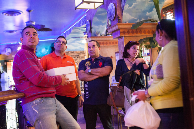 Restaurant patrons and staff, from left, Fred Ortega, Sergio Perez, Alexis Martinez and Oxandra Betancourt talk with one another and watch news reports that the United States and Cuba will normali ...
