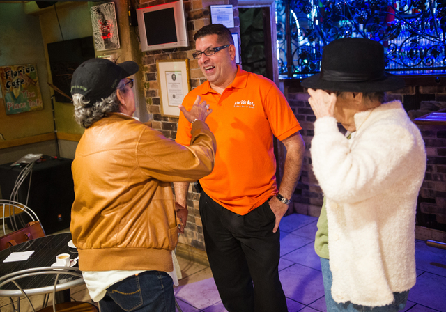 Restaurant owner Sergio Perez, center, talks with Aleyda Hernandez, owner of Aroma Cigars, left, and Angela Hernandez, about the United States and Cuba normalizing diplomatic relations, at Florida ...