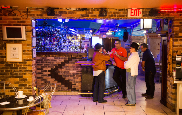 Restaurant owner Sergio Perez, second from left, talks with Aleyda Hernandez, owner of Aroma Cigars, left, Angela Hernandez, third from left, and Alexis Martinez about the United States and Cuba n ...