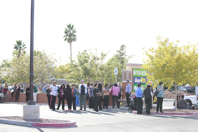 People wait as North Las Vegas Fire Department and Las Vegas Fire and Rescue and hazmat team respond to a state welfare building where people were complaining of light-headedness, at the State of  ...