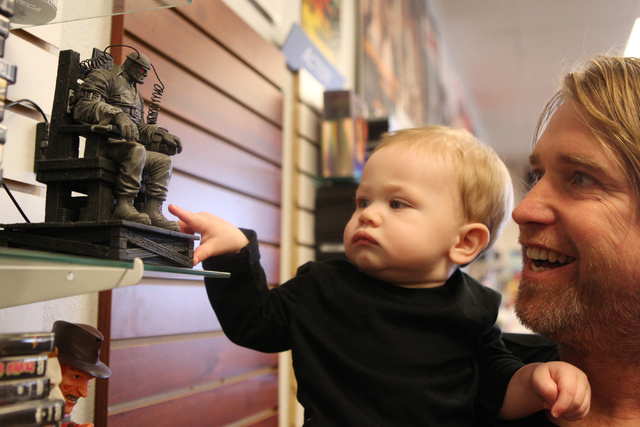 Trevor Layne, owner of Movies & Candy, 10895 S. Eastern Ave., carries his son Hudson, 1, inside his store in Henderson Tuesday, Dec. 9, 2014. The movie rental and candy shop opened two years ago a ...