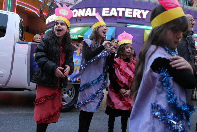 Children with the Desert Torah Academy choir from left, Rivka Harlig, 9, Elanna Sudranski, 9, and Naomi Karoudo, 7, share a laugh before their performance during the annual Grand Menorah Lighting  ...