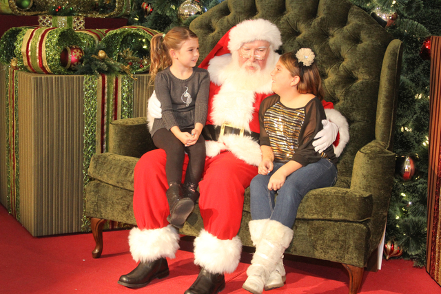 Santa Claus visits with children at the Galleria at Sunset, 1300 W. Sunset Road. The mall is set to offer photo opportunities with Santa and a nightly light shows through December 24. (Special to  ...