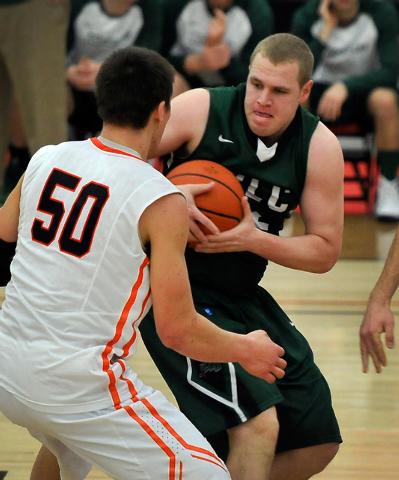 Wisconsin Lutheran forward Brett Lubbe grabs a rebound against Wartburg's Clay Cook (50) during a division III college basketball game at the South Point Arena on Tuesday, Dec. 30, 2014, in Las Ve ...