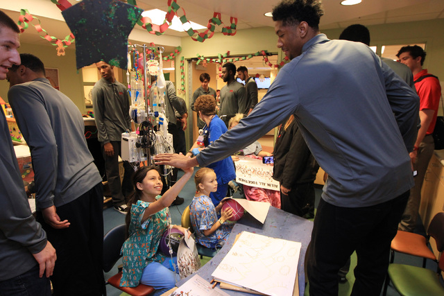 Abbigale Noh gets a high five from UNLV forward Christian Wood during a visit of the Rebels to Sunrise Children's Hospital Thursday, Dec. 18, 2014. (Sam Morris/Las Vegas Review-Journal)