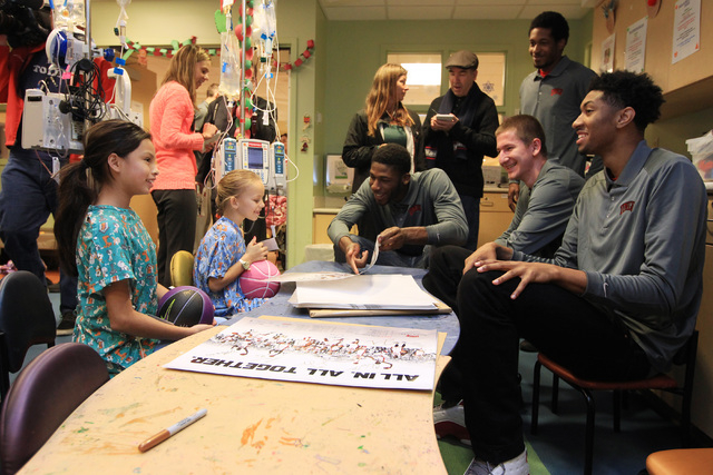 Abbigale Noh, left, and Tristen Kersey talk with UNLV's Goodluck Okonoboh, Charles Rushman, Barry Cheaney and Chris Wood during a visit of the Rebels to Sunrise Children's Hospital Thursday, Dec.  ...