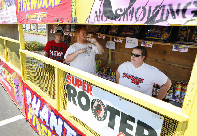 Las Vegas Wranglers Super Rooter Club President Gareth Mitchell, center, takes a drink of water while manning the club's fireworks stand in the summer heat with Ryan Leonard, left, and Kim Bjerke, ...