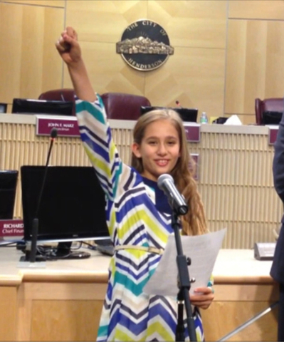 "Anya thrusts her hand into the air while delivering the final line of her speech before a recent City Council meeting: ""Anya for mayor!"" (Photo courtesy Amanda Parson)"