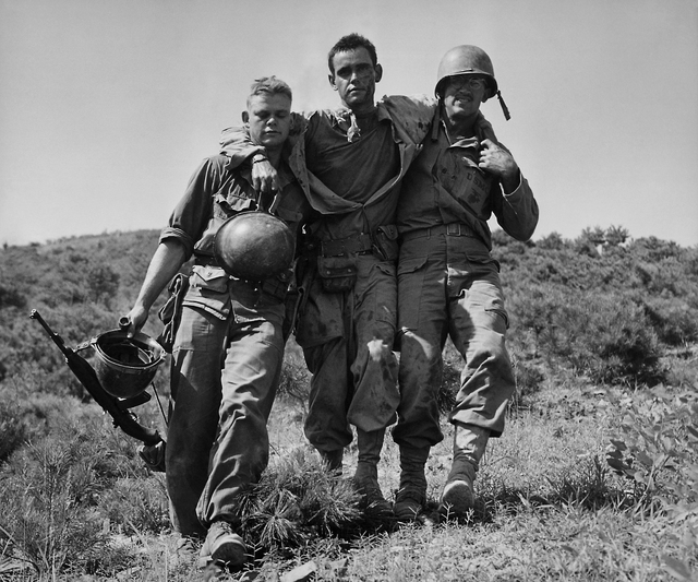 FILE - In August 1950 file photo, U.S. Marines help a wounded buddy on the Naktong River front in South Korea.  The war that began in Korea 60 years ago, on June 25, 1950, a ghastly conflict that  ...