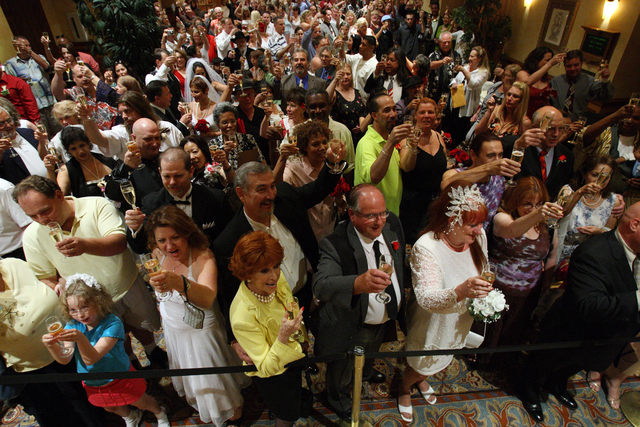 Eighty couples share a toast after getting married or renewing their vows at the Texas Station hotel-casino Saturday, July 7, 2007, on what they hope will be a lucky day. Thousands of people trave ...