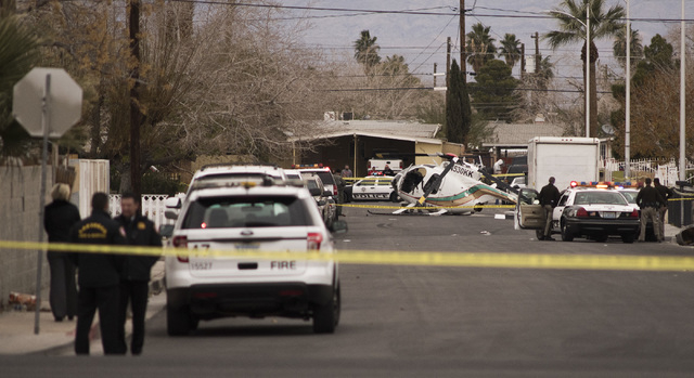 Metro police surround a Metro helicopter that came down hard on 23rd Street, about a block north of Bonanza Rd. on Wednesday, Dec. 31, 2014. (Mark Damon/Las Vegas Review-Journal)