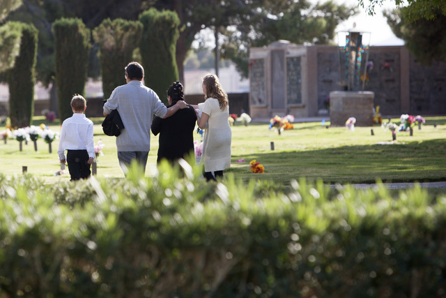 Foster parents Nicolasa Robledo-Hernandez and Jose De Jesus Hernandez walk away from the gravesite with two of their adopted children following funeral services for Michell Momox-Caselis Wednesday ...