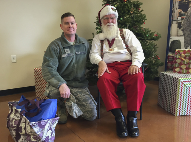 Nellis Air Force Base Staff Sgt. Corey Lewis, left, poses with Santa Claus after he stopped by Las Vegas VFW Post 10047 on Wednesday, Dec. 17, 2014, pick up an Operation Homefront gift bag for his ...