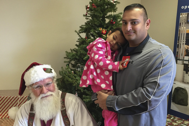 Creech Air Force Base Tech Sgt. Mike Rambaran, right, holds his daughter, Elle, 2, after they stopped by Las Vegas VFW Post 10047 on Wednesday, Dec. 17, 2014, to see Santa Claus and pick up an Ope ...