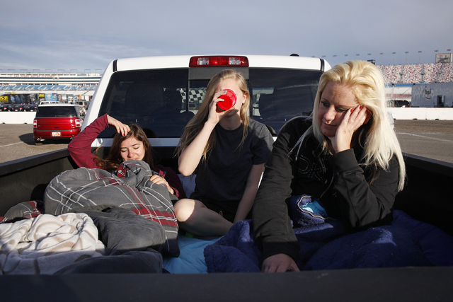 From left, Lucy Steinwender, Shyanne Beecher and Lisa Beard sit in the bed of a truck after waking up early in the morning at the Las Vegas Motor Speedway before the start of the NASCAR Kobalt 400 ...