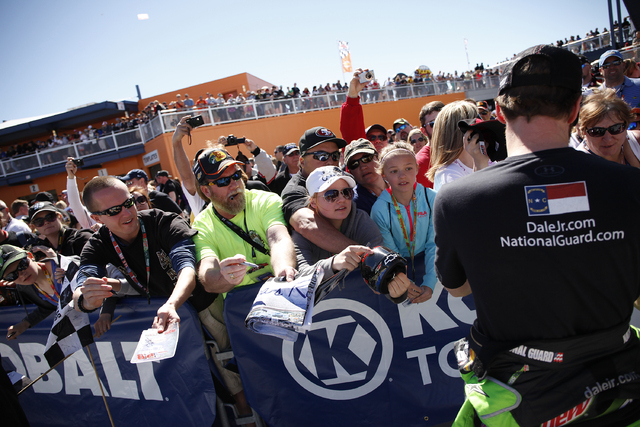 Fans try to get a autograph from Dale Earnhardt Jr., right, before NASCAR Spring Cup Series KOBALT 400 practice at the Las Vegas Motor Speedway Saturday, March 8, 2014. (John Locher/Las Vegas Revi ...