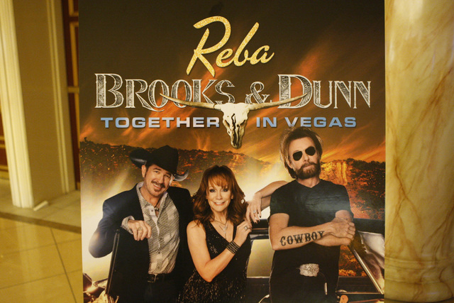 A poster with the photo of country singer Kix Brooks, from left, TV actress Reba McEntire, and singer Ronnie Dunn, is seen displayed at The Colosseum inside Caesars Palace casino-hotel in Las Vega ...
