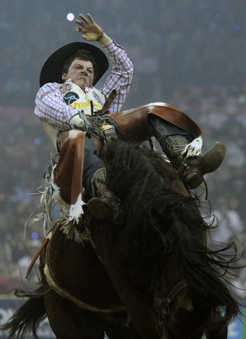 Richmond Champion of The Woodlands, Texas competes in the bareback riding during the fifth go-round of the National Finals Rodeo at the Thomas & Mack Center on Monday, Dec. 8, 2014, in Las Vegas.  ...