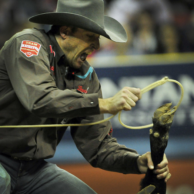 Clint Cooper of Decatur, Texas competes in the tie-down roping during the fifth go-round of the National Finals Rodeo at the Thomas & Mack Center on Monday, Dec. 8, 2014, in Las Vegas.  (David Bec ...