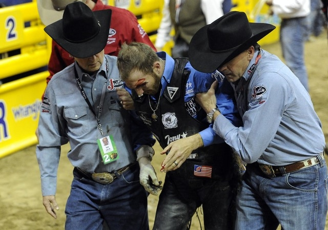 PRCA bull rider J.W. Harris is helped off the arena floor by medical staff after being injured  by Sutton Rodeos' Johnny Ringo during the eighth go-round of the National Finals Rodeo on Thursday.  ...