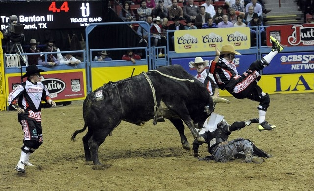 PRCA bull fighter Dusty Tuckness is tossed by Four Star Rodeo's Cyrus after Tuckness was trying to protect bull rider Trey Benton III, bottom right, during the eighth go-round of the National Fina ...