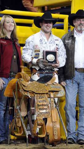 Bareback rider Kaycee Feild from Spanish Fork, Utah, is presented with the Montana Silversmith's gold buckle and a championship saddle during the tenth go-round of the National Finals Rodeo at the ...