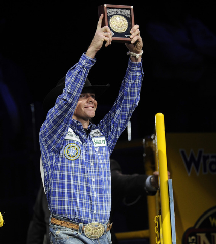 Jade Corkill from Fallon, Nev., is presented with the Montana Silversmith's gold buckle during the tenth go-round of the National Finals Rodeo at the Thomas & Mack Center in Las Vegas, Saturday, D ...