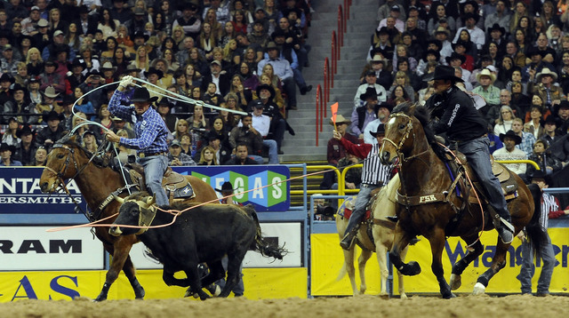 Jade Corkill from Fallon, Nev., left,and partner Clay Tryan from Billings, Mont., rope a calf to a time of 6.0 seconds during the tenth go-round of the National Finals Rodeo at the Thomas & Mack C ...