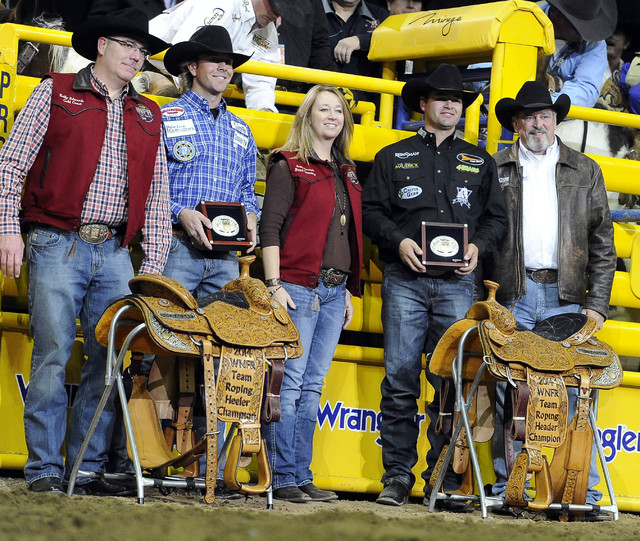 Jade Corkill from Fallon, Nev.,second from left, is presented with the Montana Silversmith's gold buckle and championship saddle with partner Clay Tryan from Billings, Mont., during the tenth go-r ...
