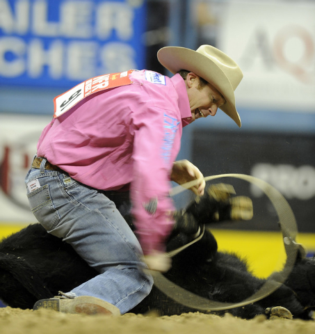 Tyson Durfey from Colbert, Wash., ties a calf to a time of 7.30 seconds during the tenth go-round of the National Finals Rodeo at the Thomas & Mack Center in Las Vegas, Saturday, Dec. 13, 2014. (J ...