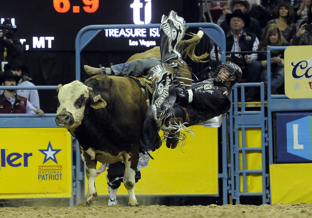 Bull rider Beau Hill from West Glacier, Mont., manages to hang onto his bull for a score 60.0 with a re-ride option during the tenth go-round of the National Finals Rodeo at the Thomas & Mack Cent ...