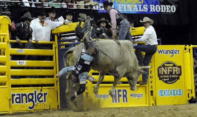 Bull rider Trey Benton III from Rock Island, Texas, is bucked off of Mr. Bull during the tenth go-round of the National Finals Rodeo at the Thomas & Mack Center in Las Vegas, Saturday, Dec. 13, 20 ...