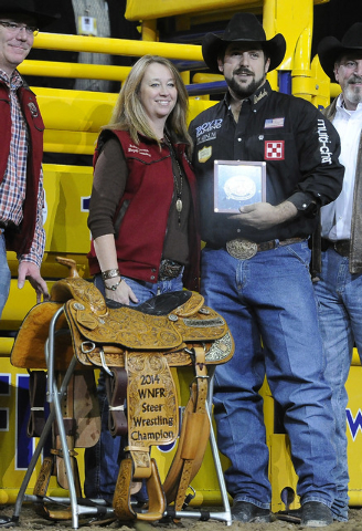 Steer wrestler Luke Branquinho from Los Alamos, Calif., is presented a gold buckle and championship saddle after winning the steer wrestling world championship during the tenth go-round of the Nat ...