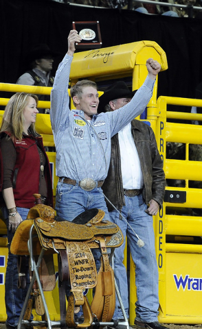 Tuf Cooper from Decatur, Texas,, is presented a gold buckle and championship saddle after winning the tie-down world championship during the tenth go-round of the National Finals Rodeo at the Thom ...