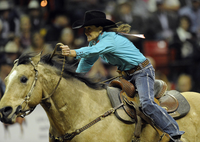 Barrel racer Lisa Lockhart from Oelrichs, S.D., rides to a sixth place time of 14.02 seconds during the tenth go-round of the National Finals Rodeo at the Thomas & Mack Center in Las Vegas, Saturd ...