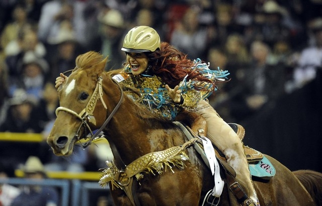 Barrel racer Fallon Taylor from Whitesboro, Texas, rides to a second place time of 13.96 seconds during the tenth go-round of the National Finals Rodeo at the Thomas & Mack Center in Las Vegas, Sa ...