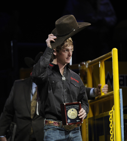 Saddle bronc rider Spencer Wright from Milford, Utah, waves to the crowd after winning the saddle bronc world championship during the tenth go-round of the National Finals Rodeo at the Thomas & Ma ...