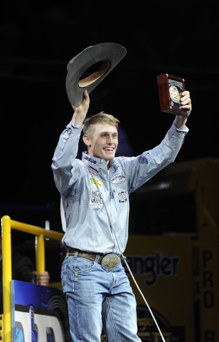 Tuf Cooper from Decatur, Texas, waves to the crowd after winning the tie-down roping world championship during the tenth go-round of the National Finals Rodeo at the Thomas & Mack Center in Las Ve ...