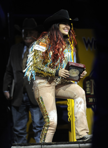 Barrel racer Fallon Taylor from Whitesboro, Texas,, waves to the crowd after winning the NFR world championship during the tenth go-round of the National Finals Rodeo at the Thomas & Mack Center i ...