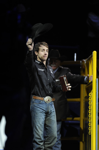 Bull rider Sage Kimzey from Strong City, Okla., waves to the crowd after winning the bull riding world championship during the tenth go-round of the National Finals Rodeo at the Thomas & Mack Cent ...