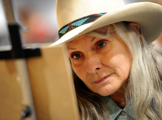 Artist Patsi Wolfe paints at her gallery booth during the Cowboy Christmas at the Las Vegas Convention Center on Monday, Dec. 8, 2014, in Las Vegas. The annual event set an all-time attendance rec ...